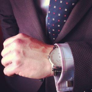 fioletowa marynarka, koszula na spinki i szwajcarski zegarek