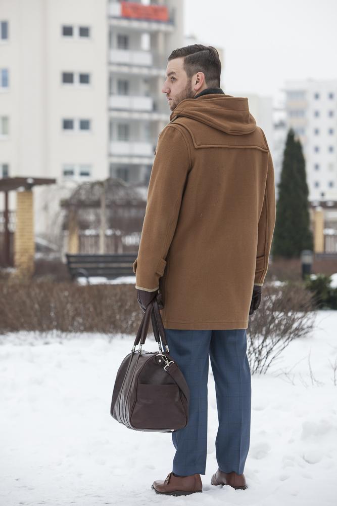 Tomasz Miler w beżowej budrysówce, niebieskich spodniach i z brązową torbą