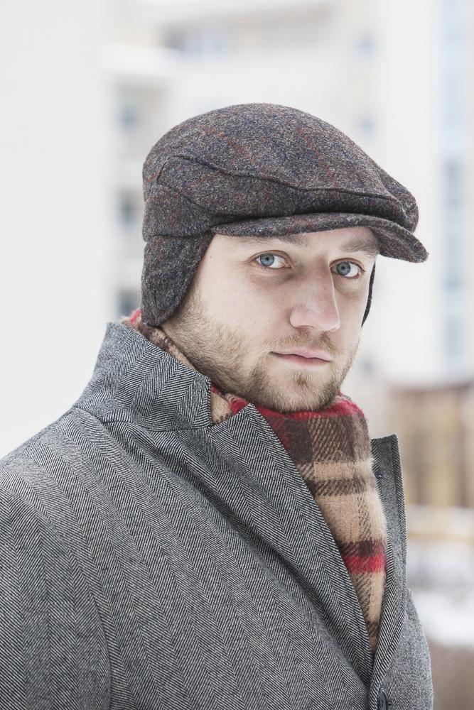 Tomasz Miler w kaszkiecie Harris Tweed, szarym płaszczu, szalik