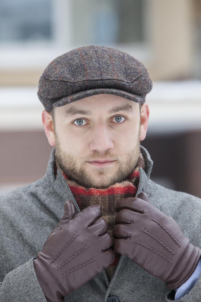 Tomasz Miler w kaszkiecie Harris Tweed, szarym płaszczu, szaliku i rękawiczkach