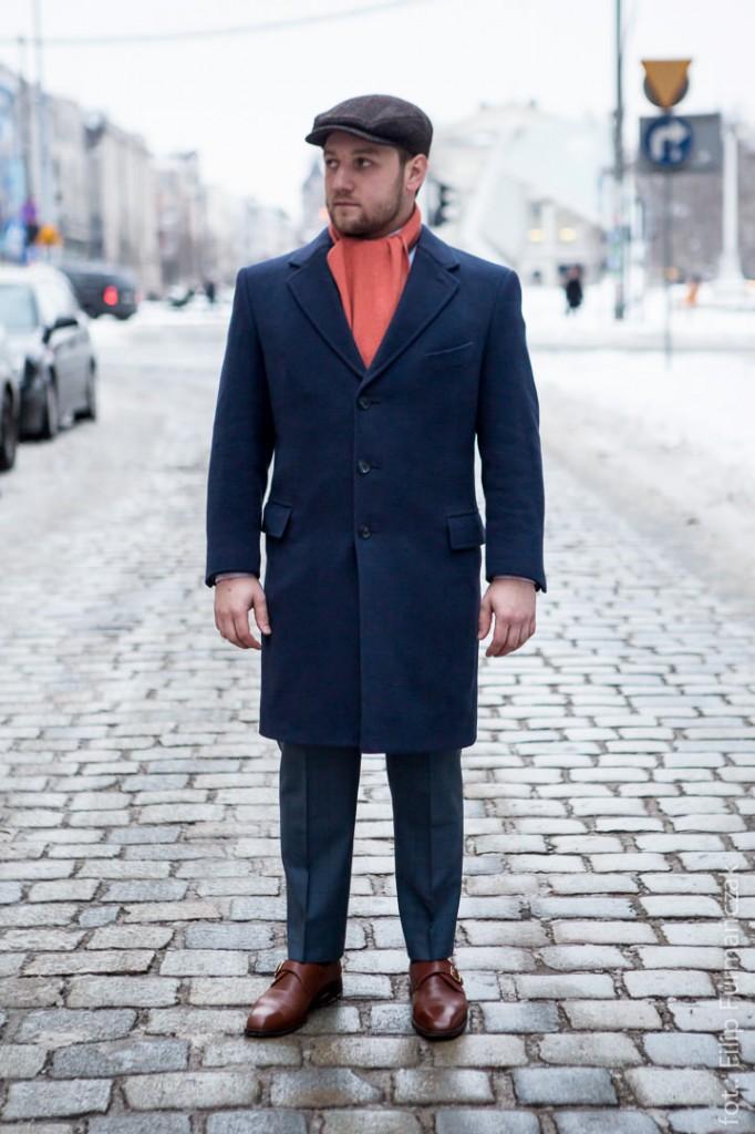 Tomasz Miler w granatowej dyplomatce, pomarańczowym szaliku i kaszkiecie z Harris Tweedu