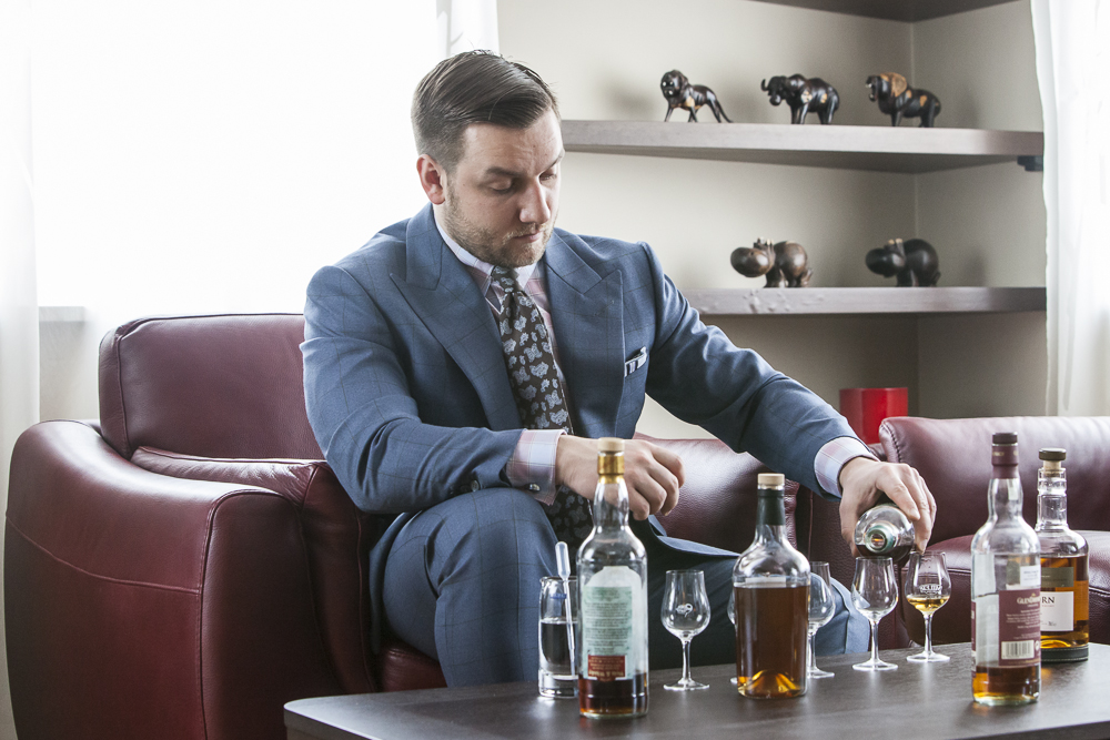 Tomasz Miler w niebieskim garniturze nalewa whisky