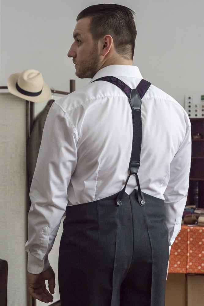 Tomasz Miler w białej koszuli, szelkach i ciemnych spodniach - od tyłu