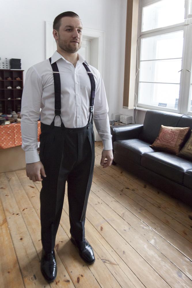 Tomasz Miler w białej koszuli i spodniach na szelki