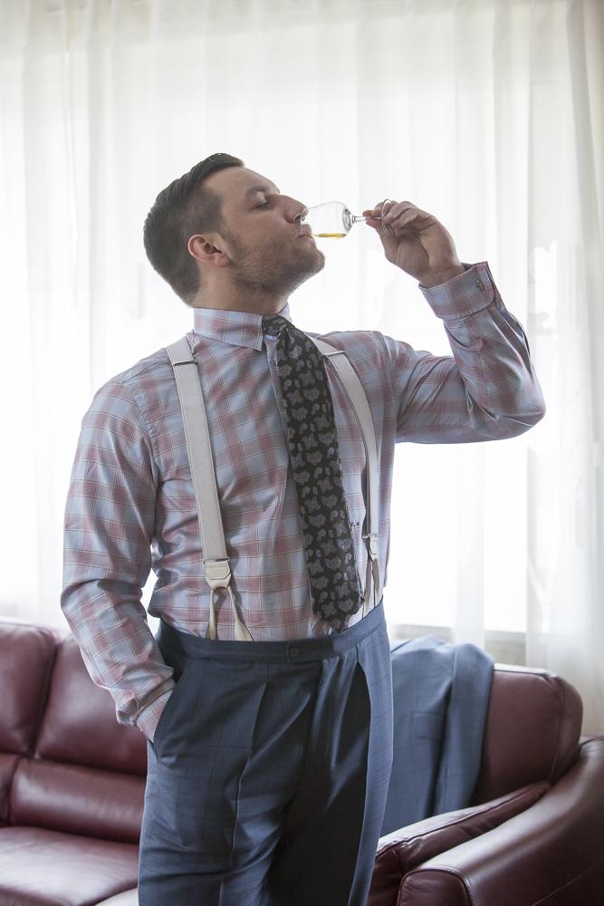 Tomasz Miler w spodniach od garnituru, koszuli i szelkach